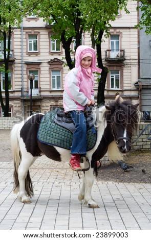 child horseback pony riding city park spring season - stock photo