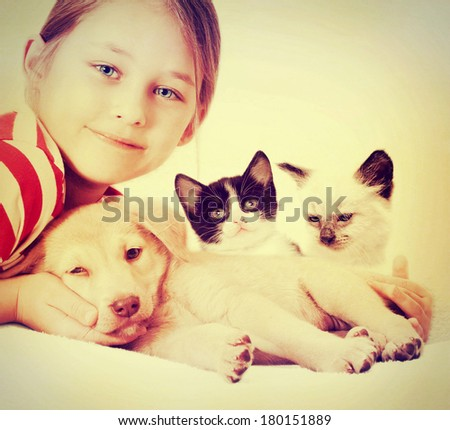 child hugging a puppy and kitten