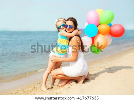Child hugging mother with colorful balloons on beach near sea - stock photo