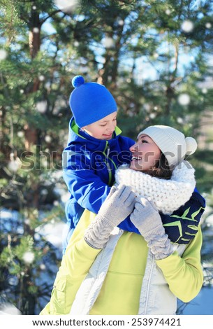 Child hugs his mom and have fun together in winter, sunny snowy day - stock photo