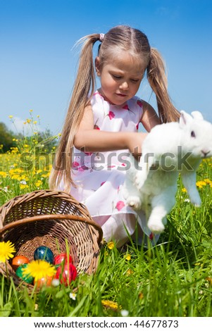Child hunting the Easter bunny on a spring meadow, eggs in a basket and lots of flowers also to be seen. The animal seems to be escaping - stock photo