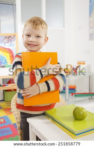 Child in a classroom with a book - stock photo