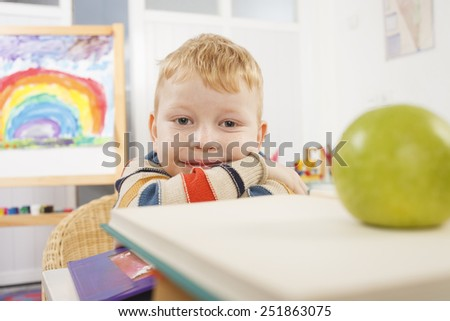 Child in a classroom with a book.  - stock photo