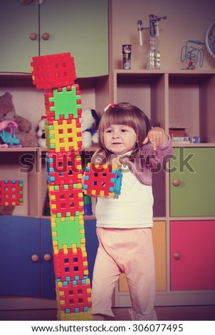 Child in a nursery built towers with blocks  - stock photo