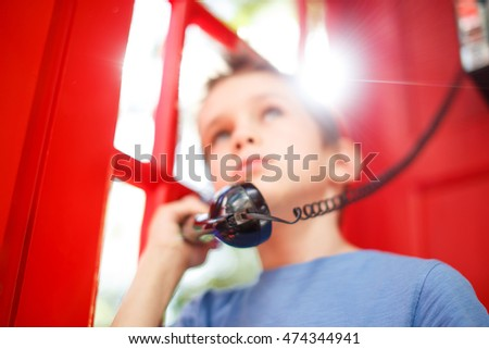 child in a red telephone box. boy talking on the phone. the concept of communication of people. soft focus. de focused, blurred background due to the concept
