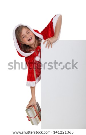 Child in a Santa costume with a board left blank for your message