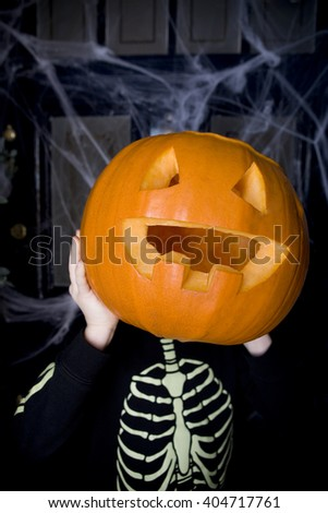 Child in a skeleton costume at a Hallowe'en party, holding a pumpkin with a carved face - stock photo