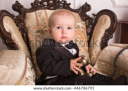 Child in a tuxedo sitting in an office talking on the phone.