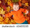 Child in autumn leaves. - stock photo