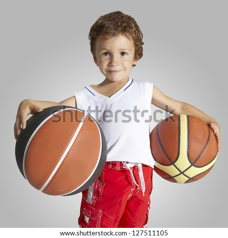 Child in basketball uniform and two balls. Young boy basketball player - stock photo