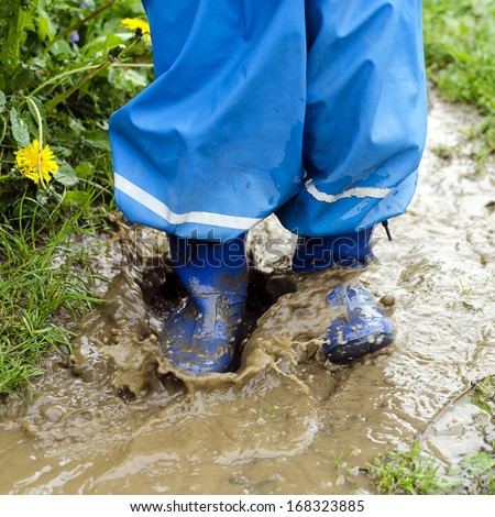Child in boots jumping in muddy puddle after rain in the garden. - stock photo