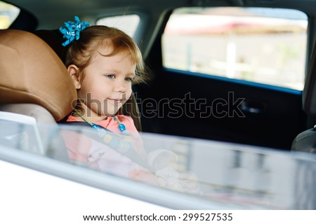 child in car in seat with belt on shoulder - stock photo