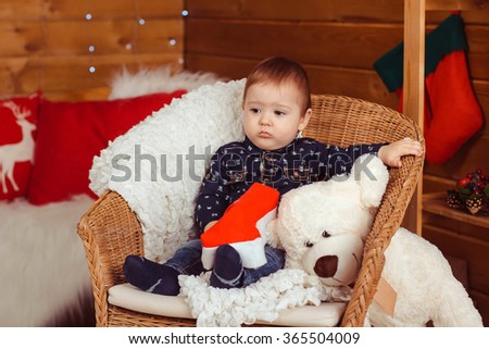 child in Christmas decorations. the little boy on the chair. the first day of the new year. Christmas.