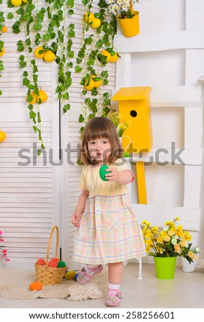 child in Easter decorations and with basket painted eggs