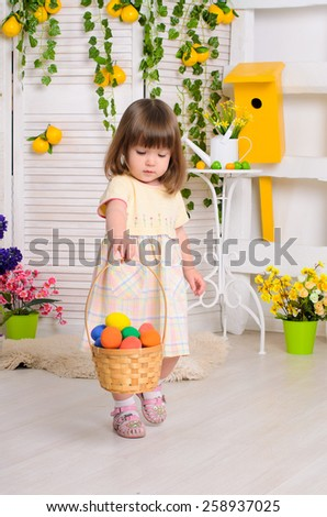child in Easter decorations and with basket painted eggs - stock photo