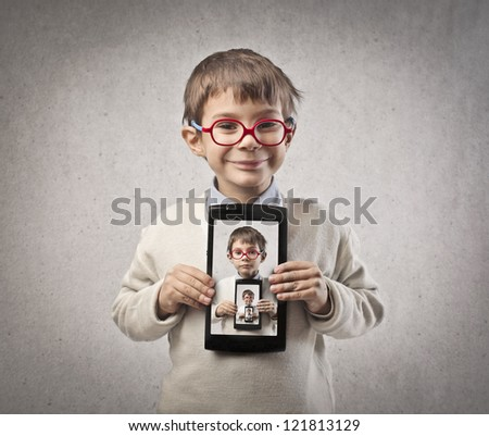 Child, in front of a mirror, with a tablet - stock photo