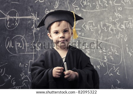 Child in grad uniform with blackboard in the background - stock photo