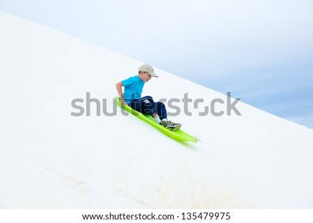 Child in green sled rolls with sand dunes .. White Sands National Monument, New Mexico - stock photo