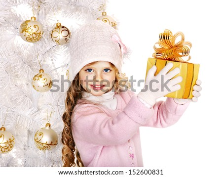 Child in hat and mittens holding gold  gift box near white Christmas tree. Isolated. - stock photo