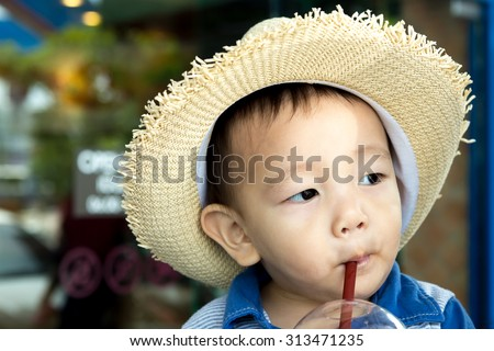 Child in hat is drinking juice - stock photo