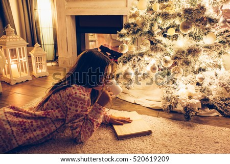 Child in pajama reading book and drinking milk on a floor by the Christmas tree in decorated room some december night, winter weekends, cozy scene