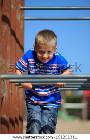 child in playground kid in action boy play on leisure equipment climbing