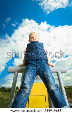 Child in playground kid in action boy playing on leisure equipment climbing - stock photo