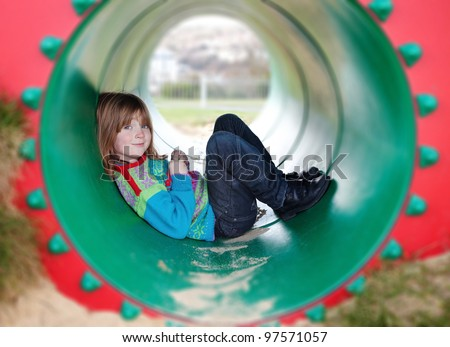 child in playground toy. boy playing in tube or pipe in park. Happy  blond kid relaxing - stock photo