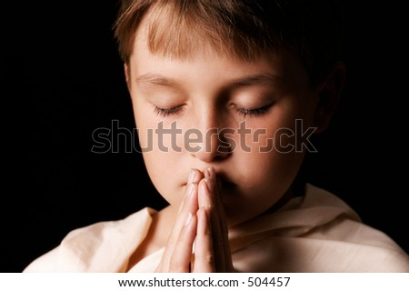 Child in prayer - horizontal softness added - stock photo