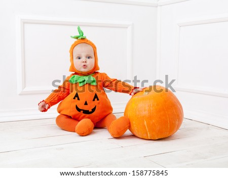Child in pumpkin suit on white background with pumpkin  - stock photo