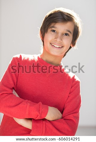 Child in red posing with sunlight on hair