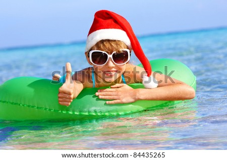 Child in santa hat  floating on inflatable ring in sea. Thumb up. - stock photo