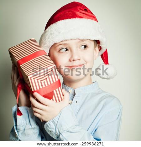 Child in Santa hat holding Christmas gift - stock photo