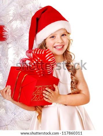 Child in Santa hat with gift box near white Christmas tree. Isolated.