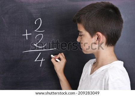 child in school blackboard with mathematical formula - stock photo