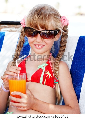 Child  in sunglasses and red bikini drink orange juice. - stock photo