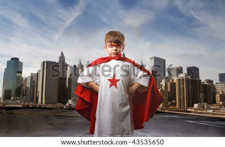 child in super hero costume and city on the background - stock photo