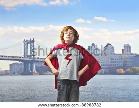 Child in superhero suit with cityscape in the background - stock photo