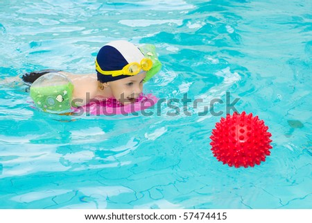 Child in swimming pool, kid swim playing water ball, little boy indoor training, 3 years old - stock photo