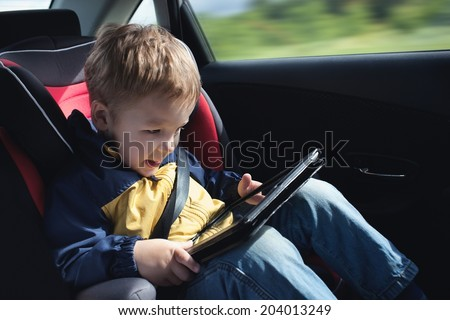 Child in the car with tablet PC - stock photo