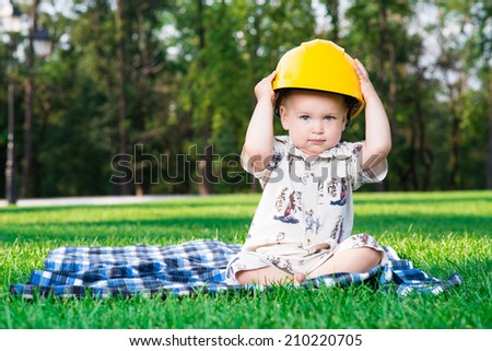 child in the construction helmet sits on a grass playing - stock photo