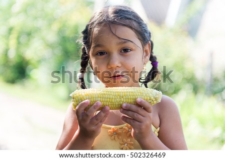 Child in the garden - lovely girl eating corn on the cob (GMO free)