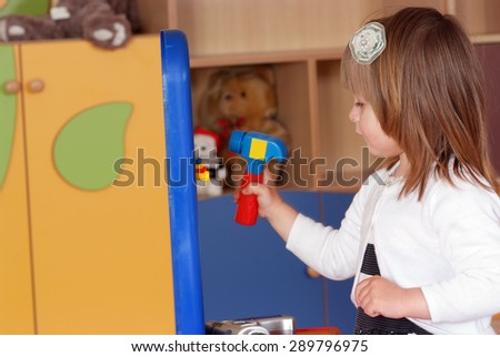 Child in the nursery is playing in building - stock photo