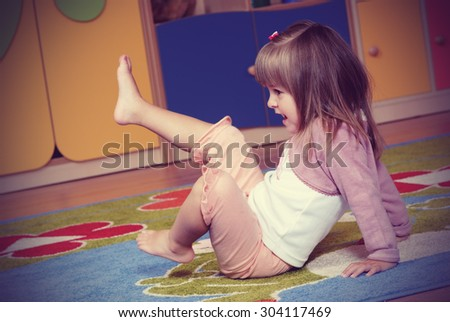 Child in the nursery playing on the colored carpet