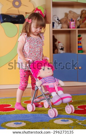 Child in the nursery playing toy doll in a stroller