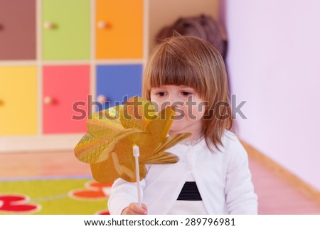Child in the nursery playing with a toy windmill