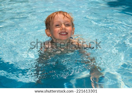 Child in the pool, looking in front - stock photo