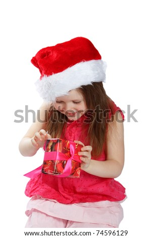 Child in the Santa hat opening a gift on a white background