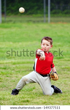 Child in uniform throwing baseball during game - stock photo