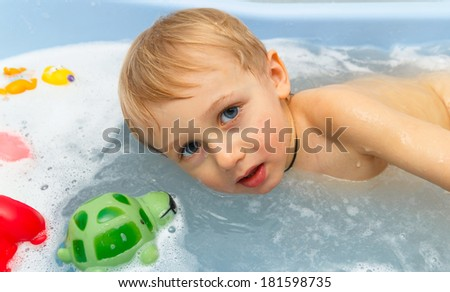 child in water in foam with toys - stock photo